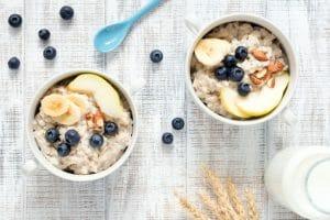 Oatmeal porridge in bowl on white table top view
